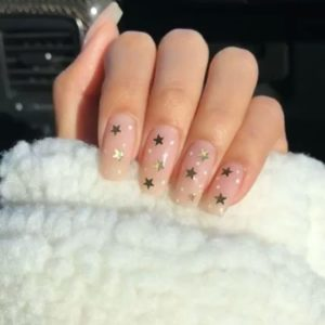 gold stars stuck over clear nails