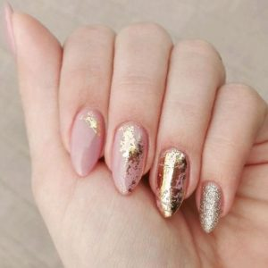 random gold foil patterns over nude nails