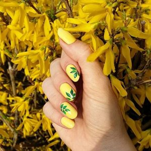 nail art of leaves on yellow nails