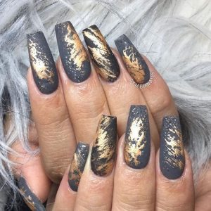 Pieces of gold foil transferred on grey nail base
