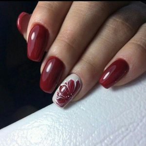 Red nails with red flower nail art on accent nail