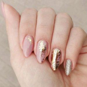 random gold foil patterns over nude nails
