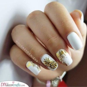 A gold pineapple on an accent nail on white base polish