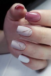 Gold curvy lines over white base polish
