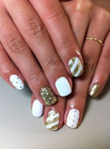 Gold stripes on white base polish on accent nails