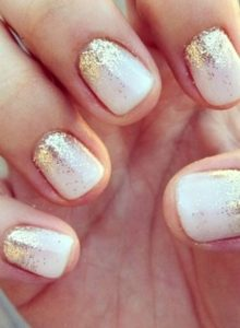 gold glitter with a gradient effect from bottom of nail on white base