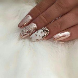 Gold studs on an accent nail on white nail polish