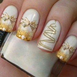 gold bow and christmas tree stickers on white nail polish coat