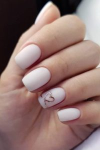 Gold heart outline on accent nail on white polish
