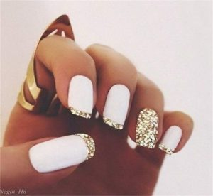 A white base polish and gold french manicure