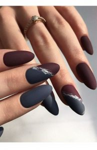 Grey and red nails with an accent nail that is half grey and half red