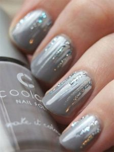 Sparkly white and silver polish strokes from nail bed